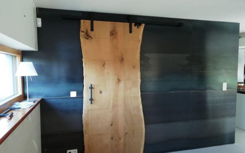 Habillage d'un mur avec de l'acier brut et porte coulissante en chêne à ANLIER